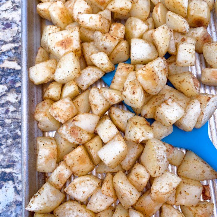 potatoes on a roasting pan with spatula