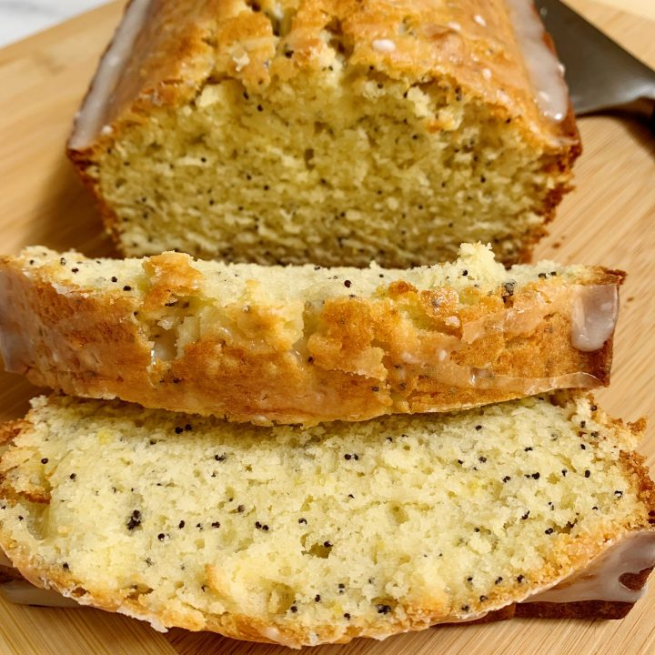 lemon poppy seed bread sliced on a cutting board