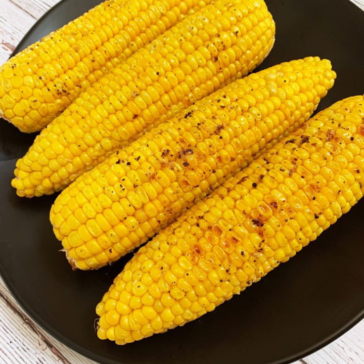 4 ears of oven roasted corn on a black plate