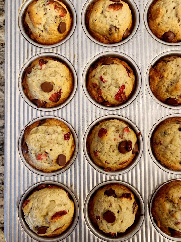 12 strawberry dark chocolate banana muffins baked in a muffin pan