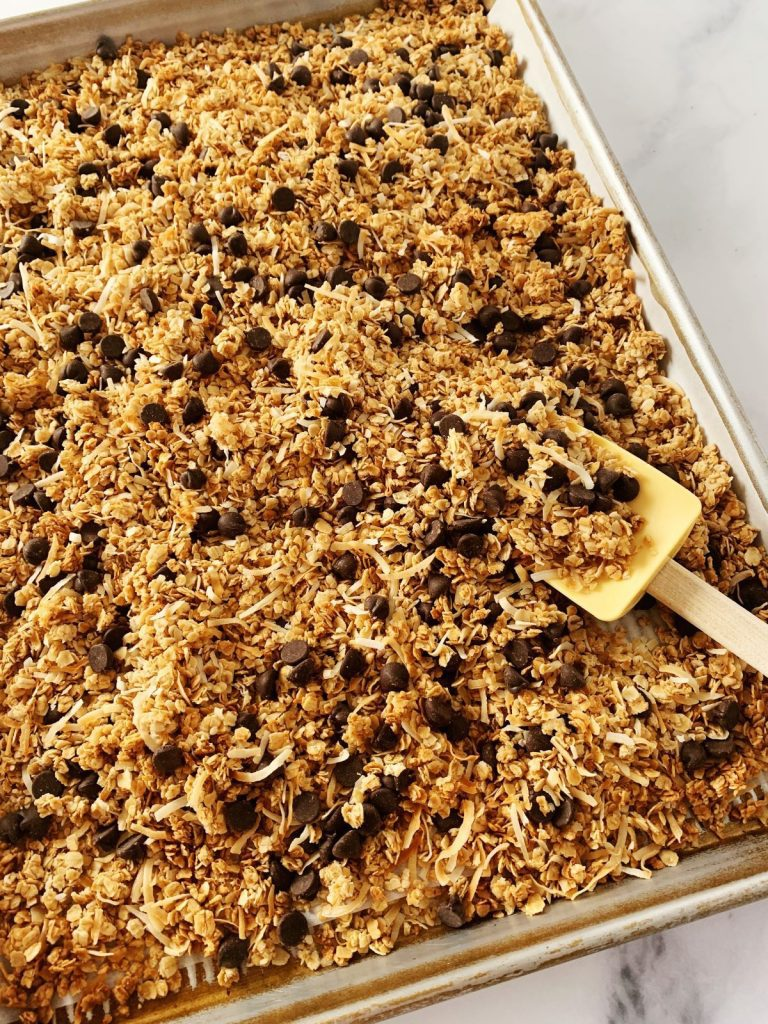 Baking sheet full of dark chocolate coconut granola with a spatula