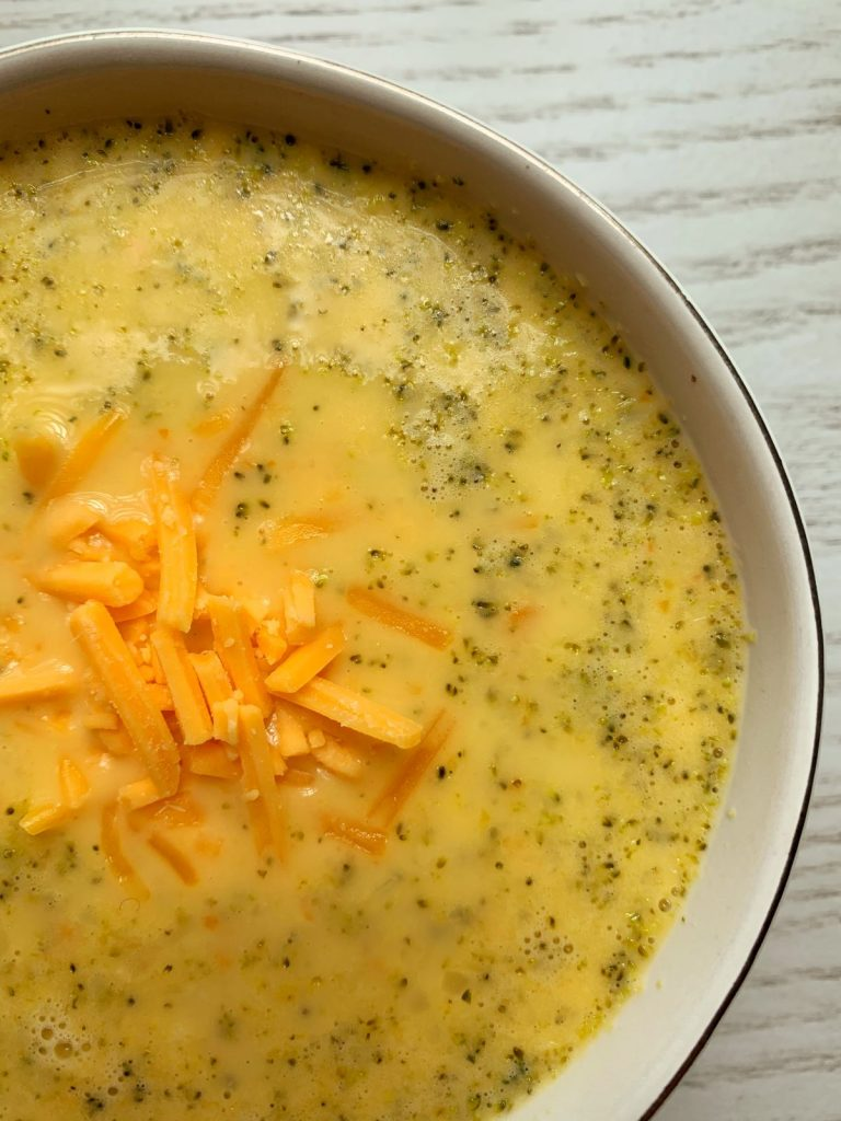 Broccoli Cheese Soup in a white bowl with extra cheese on top set on a gray counter