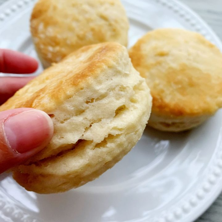 close up of a buttermilk biscuit on a white plate with 2 in the background