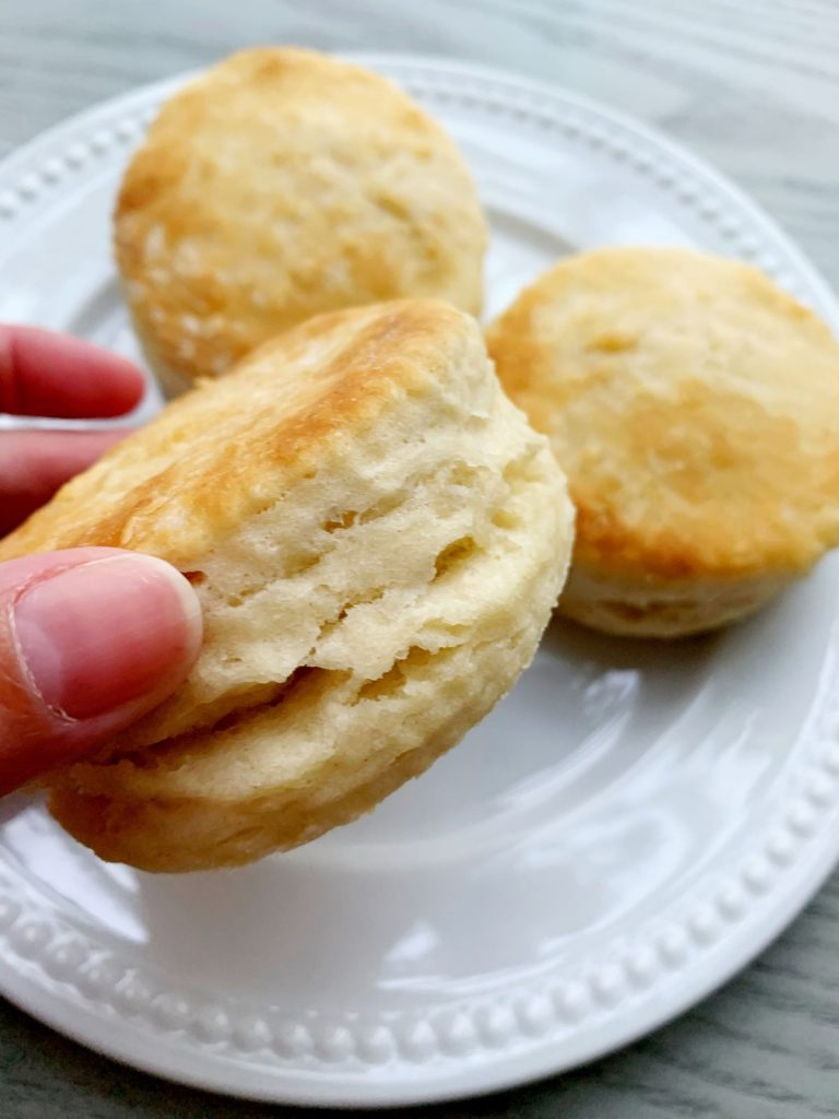 Close up picture of buttermilk biscuits with 2 others on a plate in the background