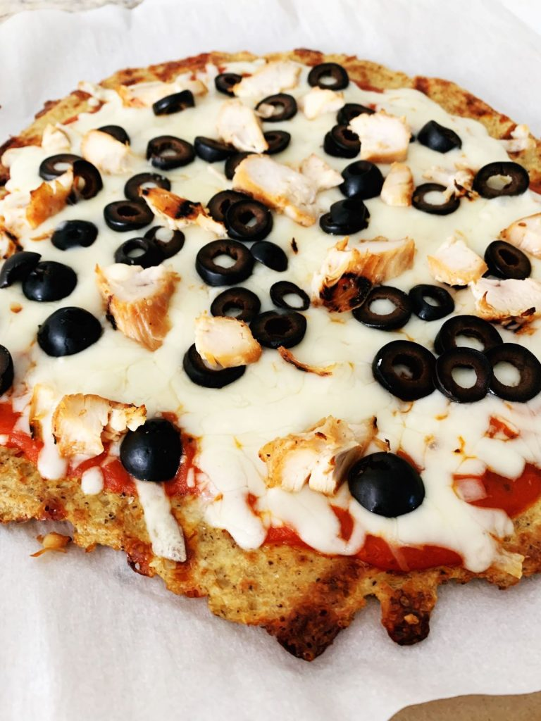 cauliflower pizza crust topped with sauce, cheese, chicken and olives
