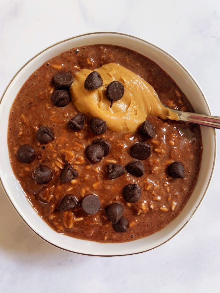 chocolate peanut butter protein overnight oats in a bowl with a scoop of peanut butter and chocolate chips on top