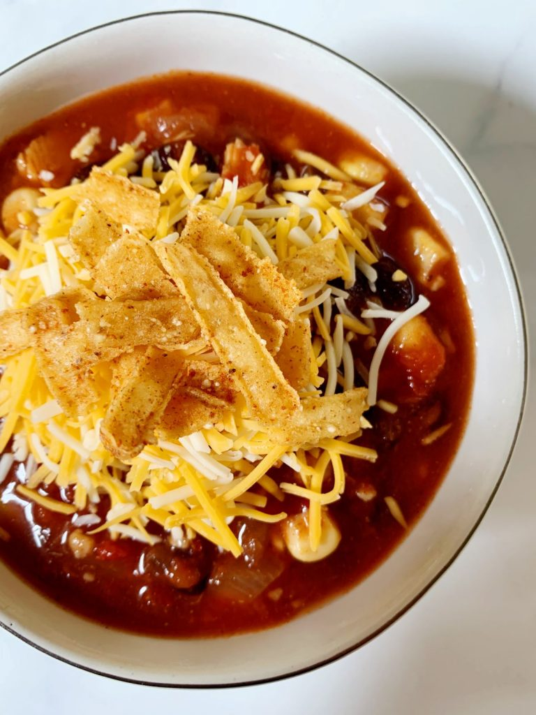 Cup of one pot black bean and corn soup topped with cheese and tortilla strips