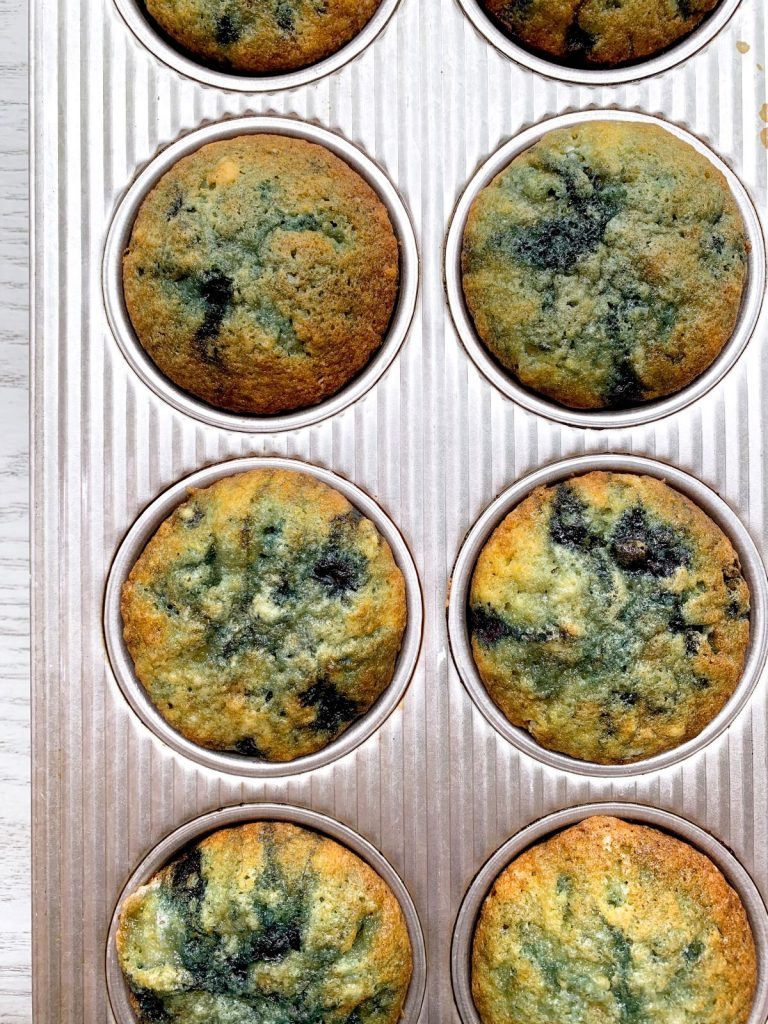 very berry blueberry muffins baked in a muffin tin