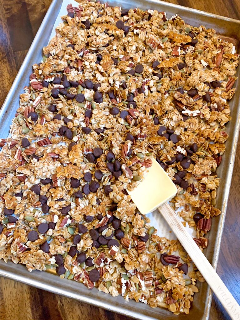 Pecan and Pumpkin Seed Granola on a baking sheet lined with parchment paper and a yellow spatula scooping some up