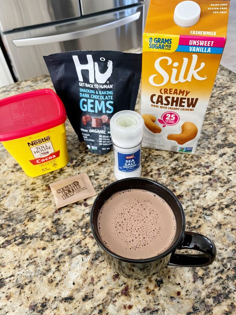 Ingredients for Homemade Vegan Salted Hot Chocolate- cocoa powder, hu chocolate, silk creamy cashew milk, sugar in the raw packets and a sea salt grinder in front of a mug of vegan hot chocolate.