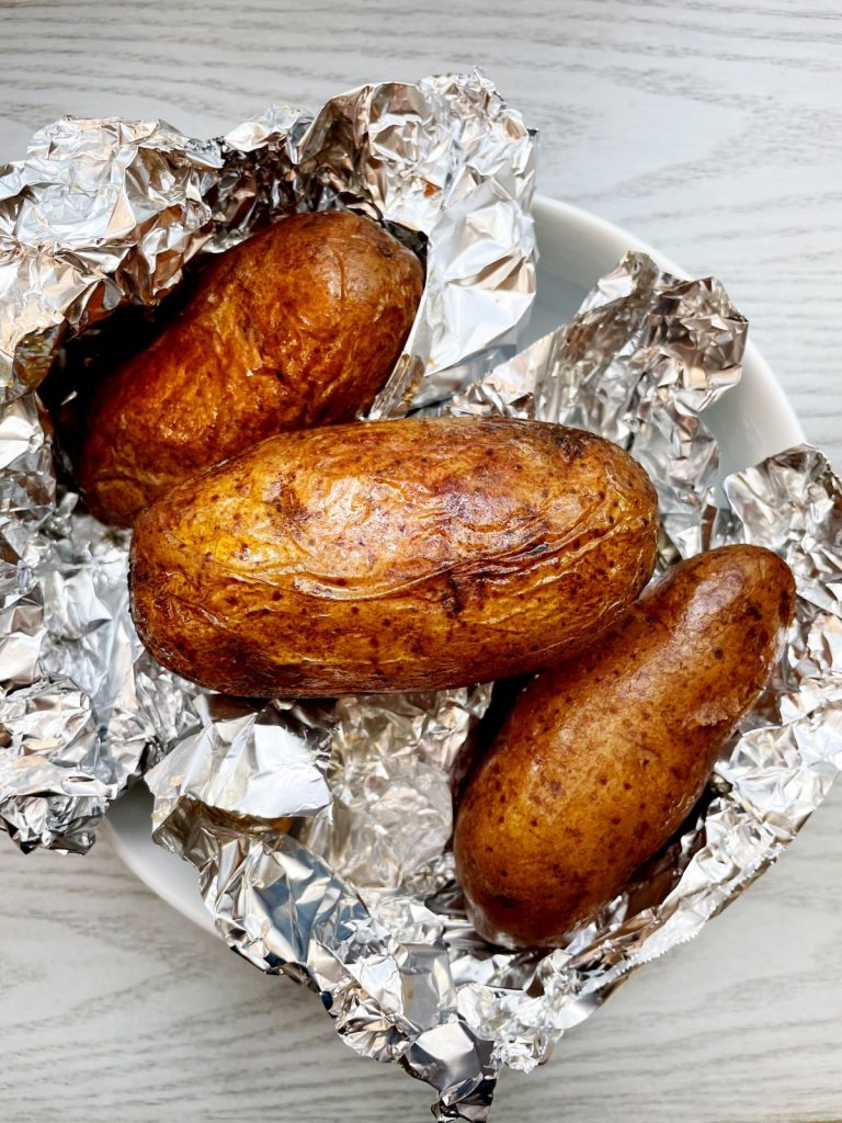 crock pot baked potatoes on top of tin foil in a bowl