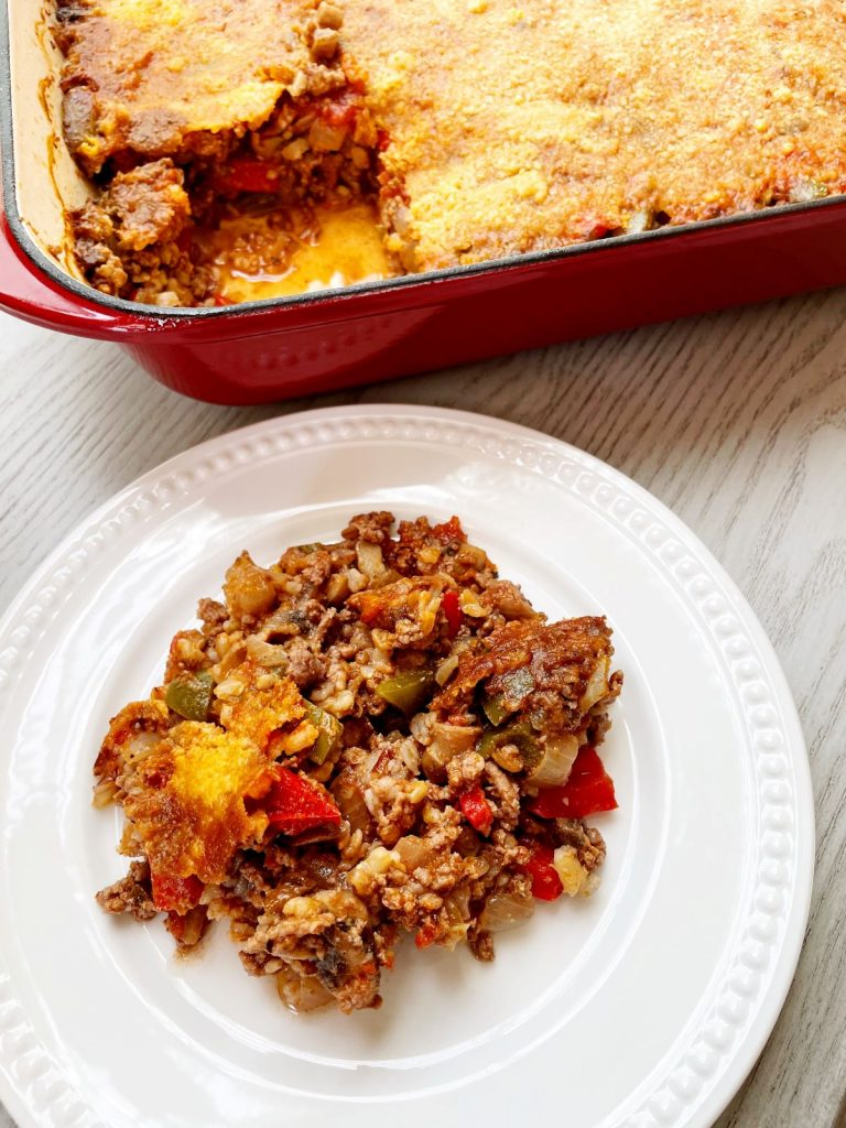 stuffed pepper casserole with beef and mushrooms on a plate with the casserole pan in the background