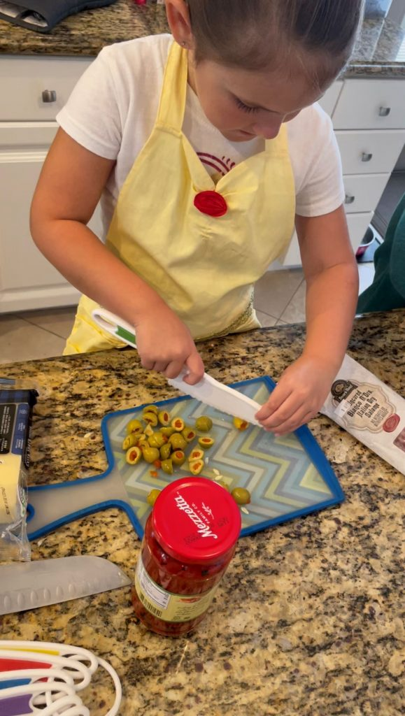 girl chopping green olives for a past salad