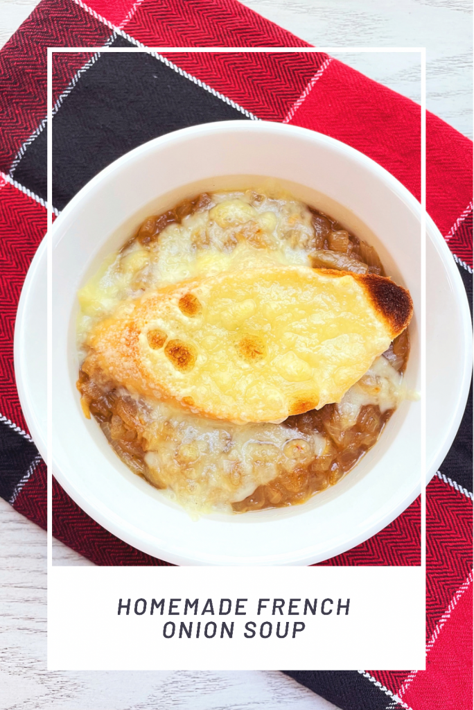 homemade french onion soup in a white bowl on a red plaid cloth