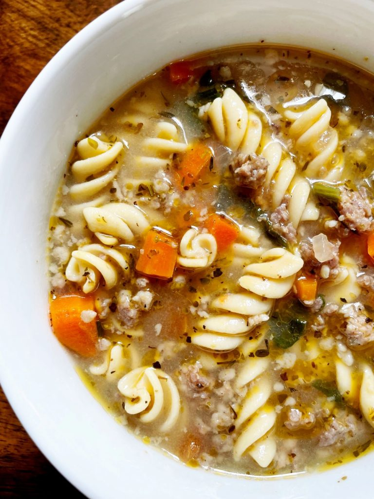 One Pot Italian Sausage and Pasta Soup in a white bowl on a wood table