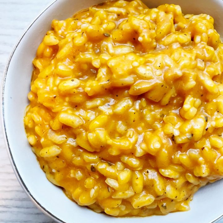 pumpkin risotto in a white bowl with a gold rim