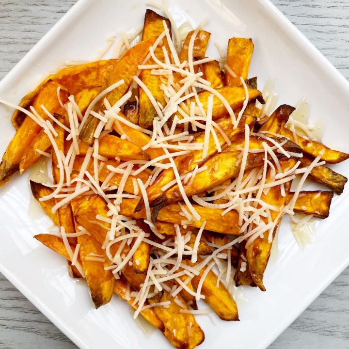 air fryer sweet potato fries on a white plate with honey and parmesan cheese
